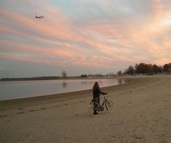 Lovely bicycle woman beach sunset plane